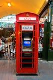 作为现钞机使用的历史的红色电话箱子在伦敦,英国 免版税库存照片