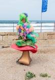 作为矮子打扮的节日的参加者坐大蘑菇 免版税库存图片
