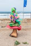 作为矮子打扮的节日的参加者坐大蘑菇 免版税图库摄影