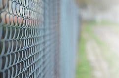 作为私有财产篱芭使用的金属网的照片  在透视的老金属栅格与一被弄脏的backgroun 免版税库存图片