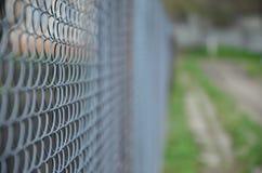 作为私有财产篱芭使用的金属网的照片  在透视的老金属栅格与一被弄脏的backgroun 免版税图库摄影