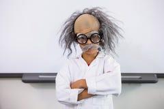 作为科学家打扮的男孩站立在教室 免版税库存照片