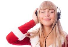作为穿戴的女孩听的音乐圣诞老人 图库摄影