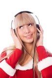 作为穿戴的女孩听的音乐圣诞老人 库存照片