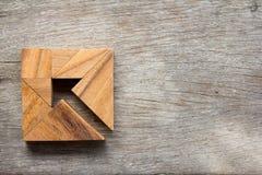 作为箭头的七巧板难题在木背景的方形的形状 库存照片