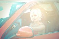 作为红色跑车驱动器的新俏丽的妇女  免版税图库摄影