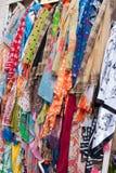 作为纪念品垂悬的许多明亮地色的围巾 免版税库存图片