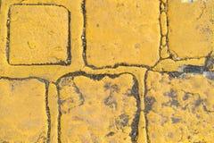 作为背景或墙纸的老黄色花岗岩路立方体 库存图片