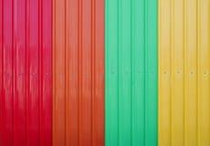 作为背景的红色橙色绿色黄色波纹状的金属板 库存图片