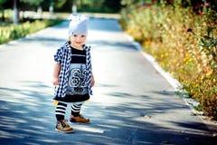 作为臀部跳跃者打扮的小女孩是在一条道路在公园 免版税库存照片