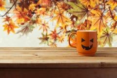 作为起重器o灯笼南瓜的咖啡杯在秋天背景的木桌上 免版税库存照片