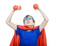 作为超人打扮的美丽的滑稽的孩子努力与小dubbells一起使用 库存图片