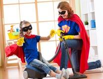 作为超级英雄和母亲打扮的孩子使用吸尘器在屋子里 家庭中年妇女和女儿获得一个乐趣 免版税库存照片