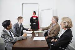 作为超级英雄的商业领袖在同事前面在会议上在会议室 图库摄影