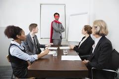 作为超级英雄的商业领袖在同事前面在会议上在会议室 免版税图库摄影