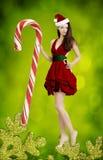 作为逗人喜爱的圣诞老人女孩的美丽的少妇 图库摄影