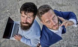 作为配合的企业精神 与解决问题的膝上型计算机和电话的商人做成交 免版税库存图片