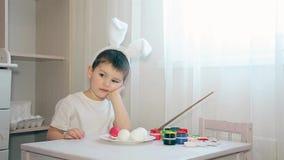 作为野兔打扮的男孩不知道装饰复活节彩蛋的颜色的什么颜色 影视素材