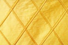 作为金黄背景的织品 库存照片