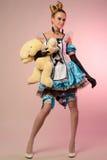 作为阿丽斯打扮的一个少妇的画象在妙境,用一只兔子在手上 免版税图库摄影