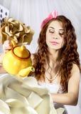 作为阿丽斯打扮的少妇在有大水壶和花的妙境 库存图片