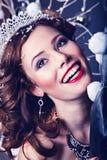 作为雪女王/王后字符的圣诞节微笑的妇女 免版税图库摄影