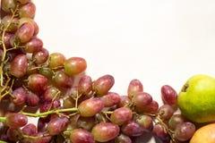 作为顶面框架被安排的葡萄在白色木背景附近 与大量的顶视图拷贝空间 库存图片