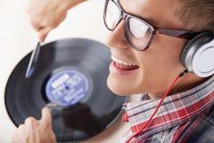 作为dj的年轻人工作有耳机和圆盘的 库存图片