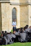 作在大教堂地面的凉快的老师演讲  库存图片