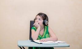 作坐在桌后和看与耳机的小俏丽的女孩在她的头 免版税库存图片