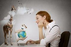 作坐在计算机前面的妇女,有来自膝上型计算机屏幕的地球的手 免版税库存照片