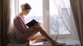 作女孩读在家坐在窗口基石的书 外部冬天 股票录像