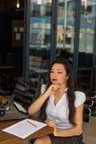 作家女性工作在使用减速火箭的一个室外咖啡馆打字 库存图片
