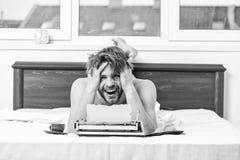 作家每日惯例  人作家与早餐工作的位置床 作家英俊的作者使用了古板的指南 图库摄影