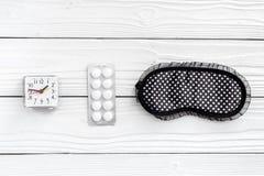 作战失眠 近安眠药睡觉面具和闹钟在白色木背景顶视图 免版税图库摄影