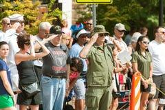 作战退伍军人向美国国旗致敬在老战士天游行 免版税库存照片