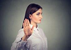 作报告的恼怒的妇女与向外的棕榈的手势 库存图片