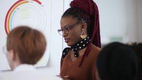 作报告的镜片的特写镜头愉快的年轻确信的非洲女商人同事在现代轻的办公室 股票视频