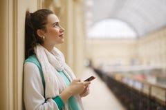 作梦与智能手机的妇女在她的手上 免版税库存图片