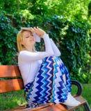 作梦关于愉快的末端 女孩坐放松与书,绿色自然背景的长凳 读的夫人俏丽书痴梦想 免版税库存图片