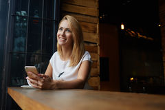 作梦关于某事的年轻愉快的妇女,当坐与在现代咖啡店时的巧妙的电话, 库存图片