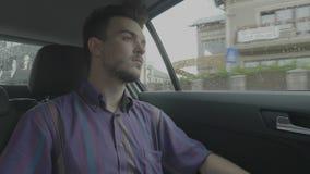 作梦和看通过在他的城市乘驾的车窗的忧郁的年轻人在阴沉的下雨天- 股票录像