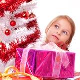 作梦在一个白色圣诞节结构树之后的女孩 库存图片