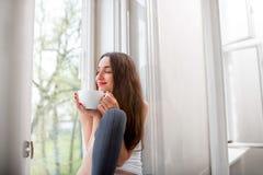 作梦在与杯子的窗台的年轻和逗人喜爱的夫人coffe 免版税图库摄影