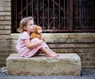 作梦在与玩具熊的具体步鄹的小女孩 免版税图库摄影