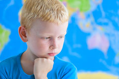作梦在世界地图前面的学龄前男孩 免版税库存图片