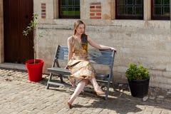 作梦在古色古香的房子前面的长凳的女孩 免版税图库摄影