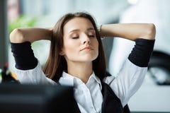 作梦在工作场所的快乐的女实业家 女性办公室工作者作为在被做的工作以后打破 放松在的企业夫人 免版税库存照片