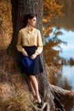 作梦在秋天季节的河附近的妇女 库存图片