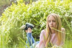 作梦在草的一个晴天的逗人喜爱的白肤金发的少年女孩 库存图片